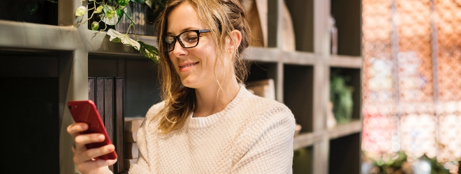 White, 30-something woman with glasses looking at her smartphone smiling in front of bookshelves