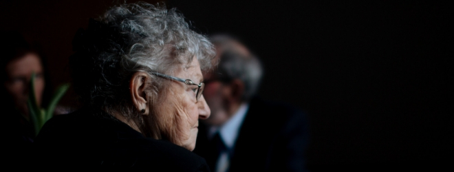 Profile picture of a senior woman's, looking vulnerable on a black background