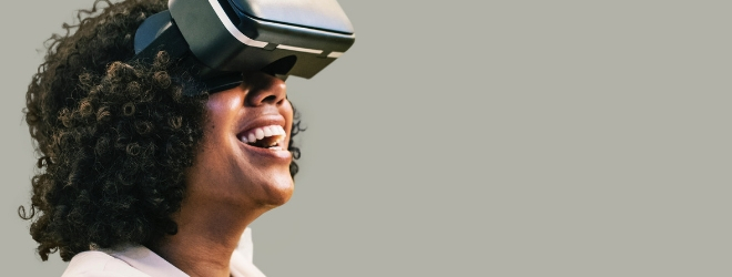 A woman wears a virtual reality headset, she's looking up and smiling