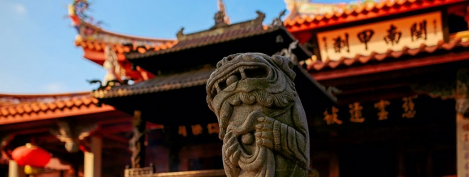 A statue representing a Japanse deity is at the center, a temple is in the background